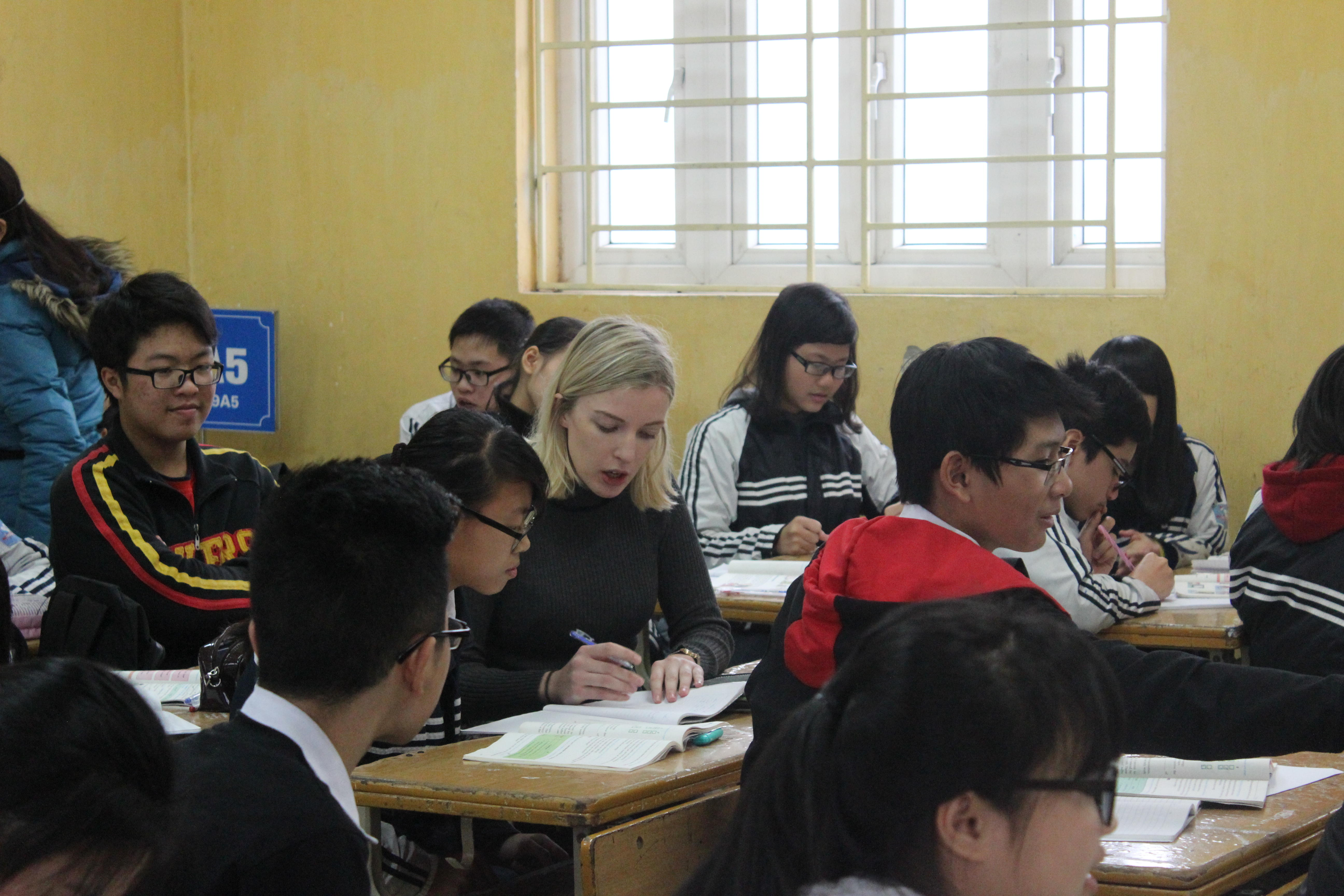 A French teaching volunteer assists a student at a placement in Vietnam