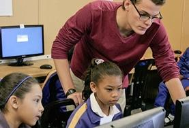 A Teach IT volunteer demonstrates important computer skills to a young girl at a school in South Africa.
