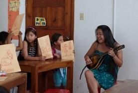 A volunteer and students play musical instruments together