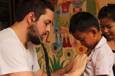 Projects Abroad Medicine volunteer treats a young boy as part of a medical outreach programme in Phnom Pehn, Cambodia